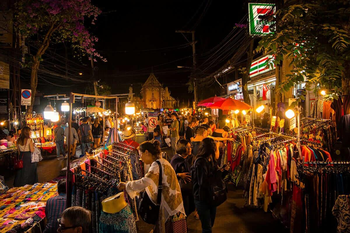 crowds and stalls outside seven eleven at the chiang mai sunday night market