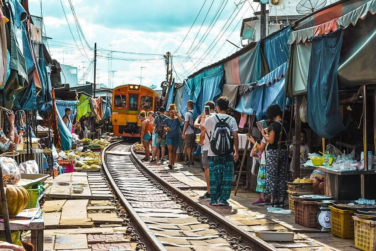 train driving through market on railway tracks bangkok to chiang mai