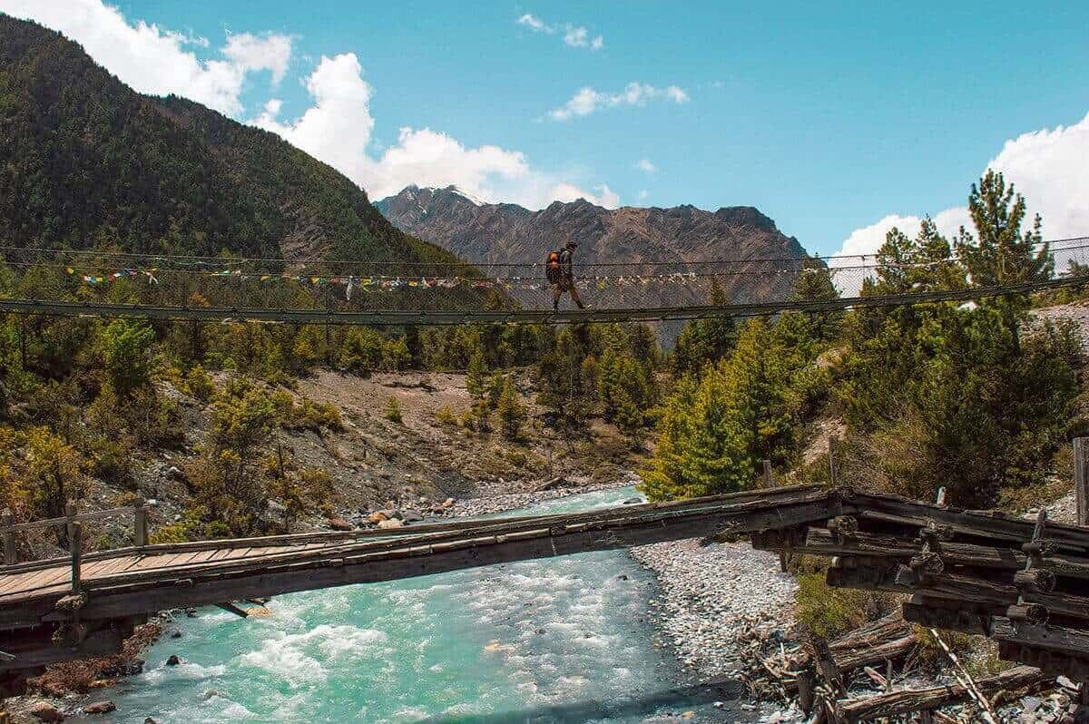 hikiing over a bridge with icy water underneath on the annapurna circuit