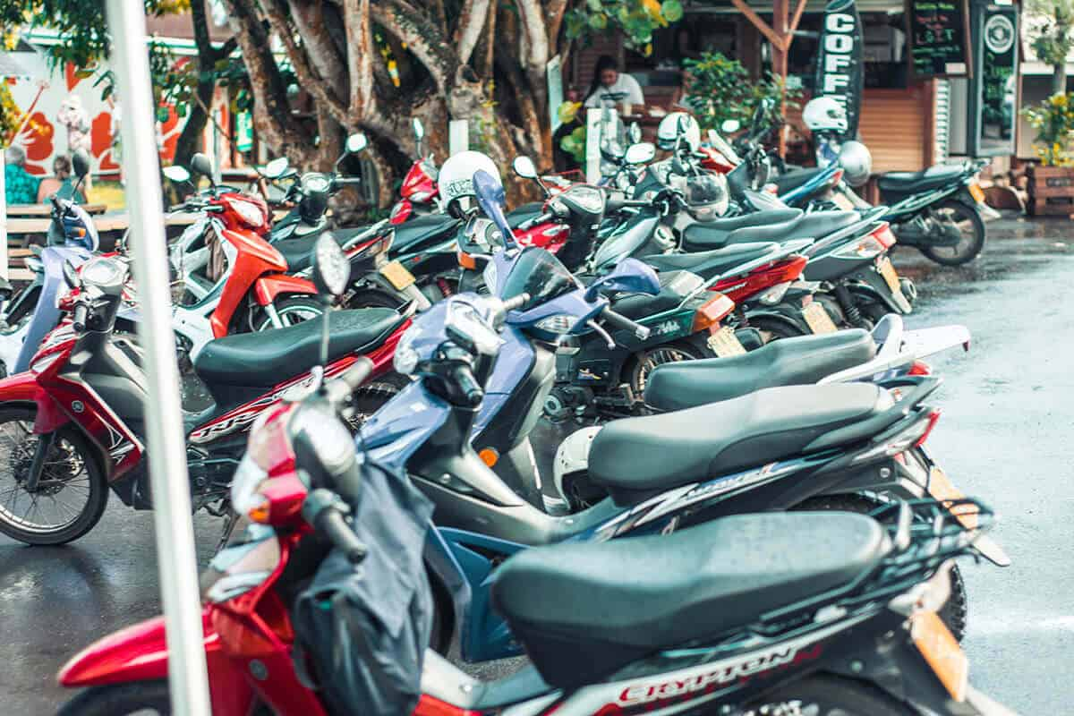 an assortment of scooters parked outside the market in rarotonga